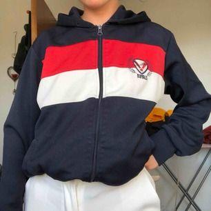Mörkblå hoodie med luva, tryck på ryggen med vita och röda detaljer. Köpt second hand