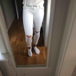 Vita jeans med hål på knäna i 34 från Gina Tricot