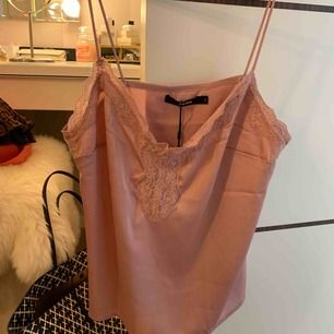Rosa linne från Bik Bok med spetsdetaljer. Aldrig använt linnet så den är i nyskick! Prislappen sitter även kvar.
