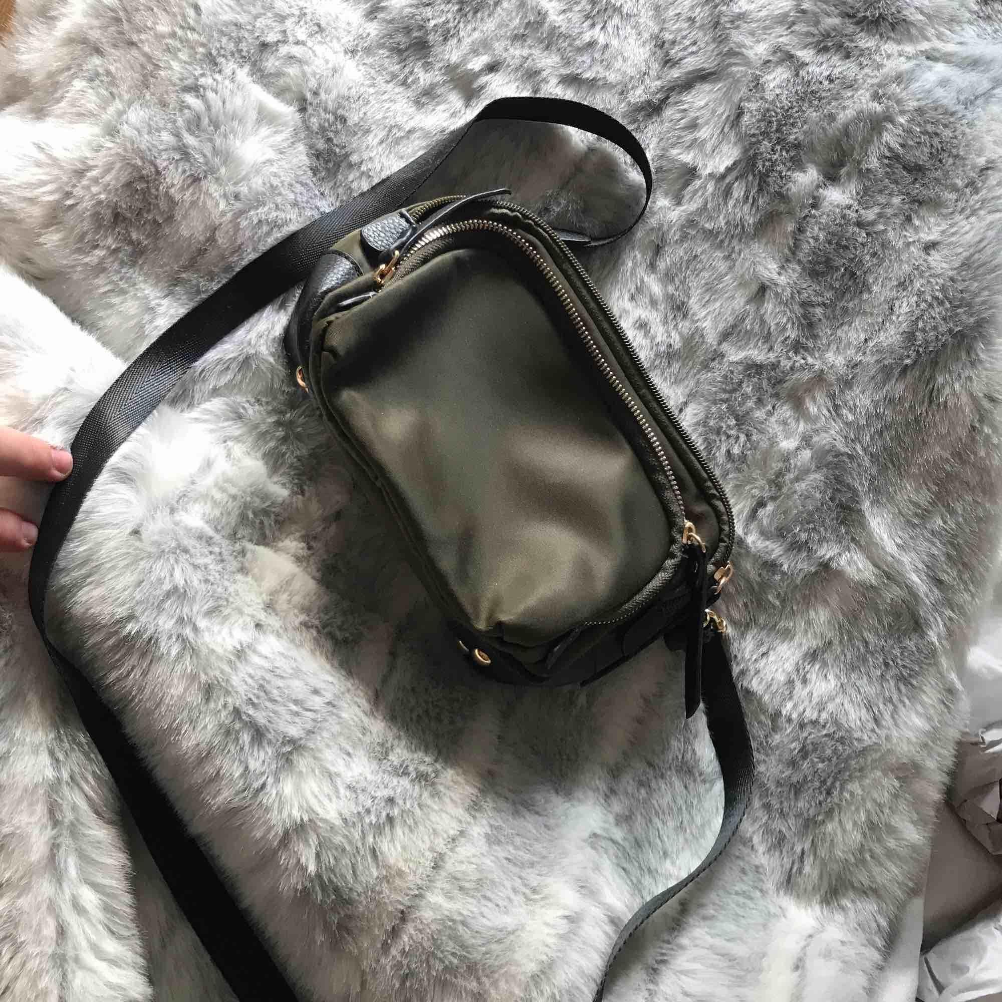 En mörk grön väska som aldrig använd från Nelly. Väskor.