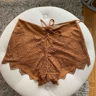 Otroligt fina shorts i mocka liknande material med cut out detaljer. Storlek S, frakt tillkommer.