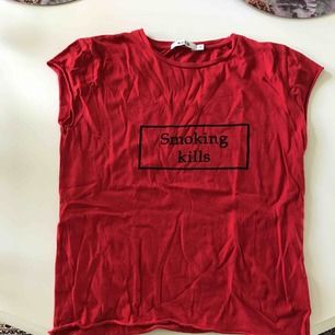 """En jätte cool T-shirt från Na-kd i strl S med texten """"smoking kills"""". Den är i mycket bra skick och inte använd så jättemånga gånger. :) Säljes pga har ingen användning av den längre."""