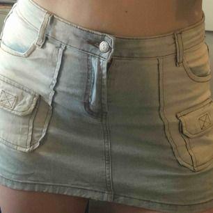 Kort kjol i jeansliknande tyg. Stretchig med 4 stora fickor och 2 små. Köpt på second hand i Berlin! Har en liten slits på båda sidor.
