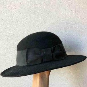 Svart stor hatt i filttyg