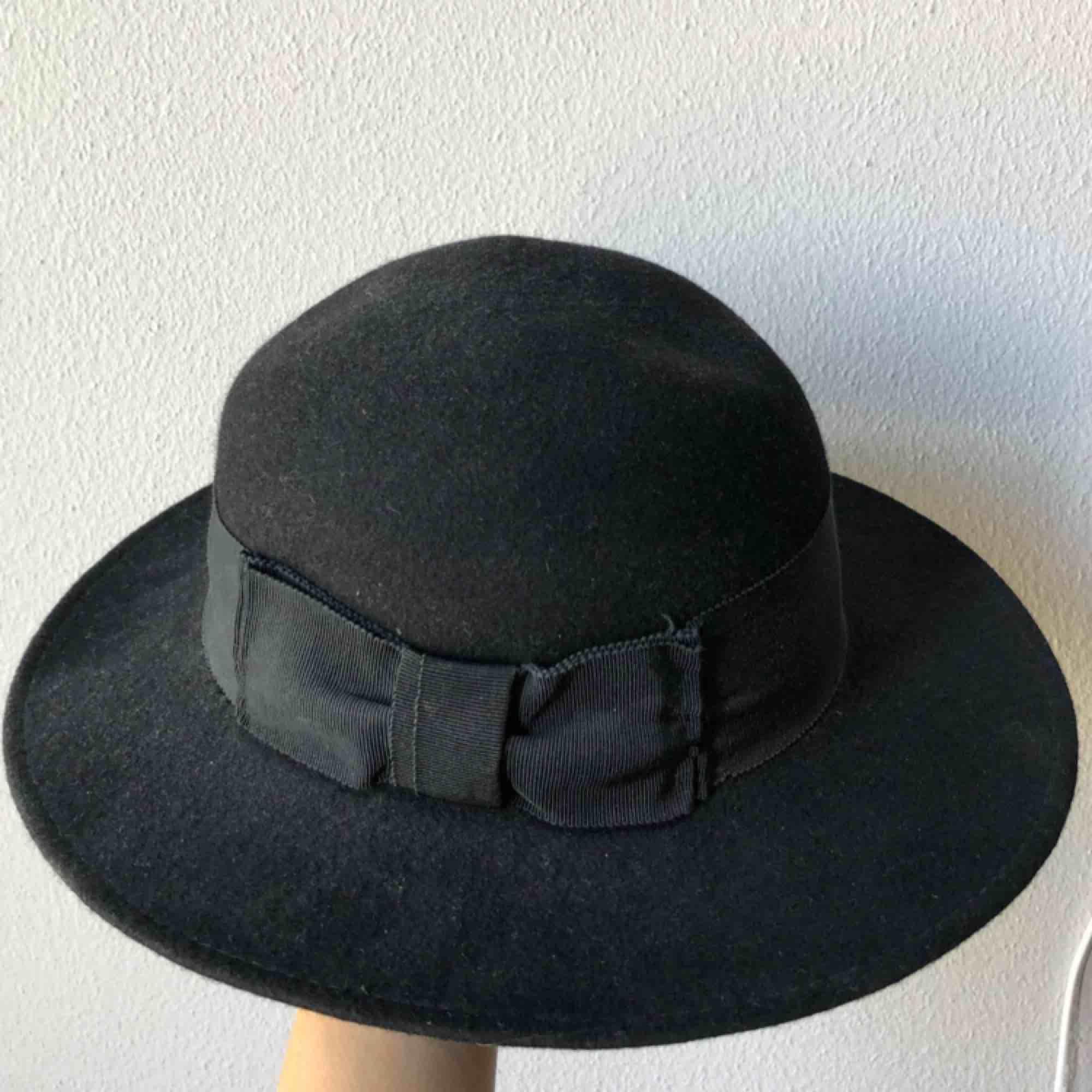 Svart stor hatt i filttyg. Accessoarer.