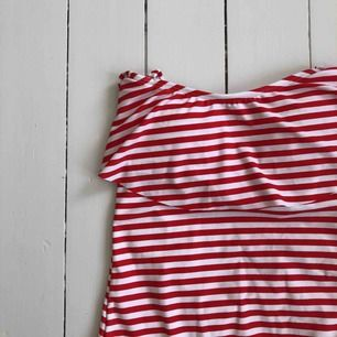 Röd - vit randig baddräkt. Aldrig använd, super skick. Baddräkten är offshoulder & har ett knäppe + band som man knyter runt nacken, men dessa band är avtagbara. Den har också inlägg som man kan ta av & på.