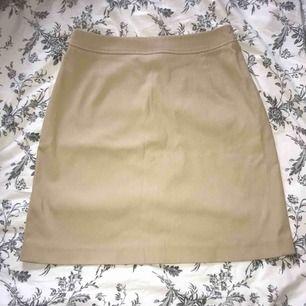 Beige kjol med dragkedja och fickor bak. Tror att det är köpt på MQ för typ 20 år sen. Lite sliten på ett ställe vid dragkedjan annars bra skick.