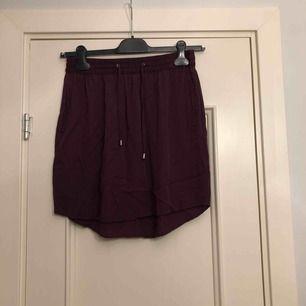 Mörklila/vinröd bekväm kjol från Åhléns i storlek 38. Använd fåtal gånger men i mycket bra skick! 80 kronor inkl frakt!