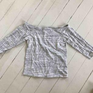 En off shoulder tröja från Bik bok i strl M. Är i färgen ljusgrå och vit.