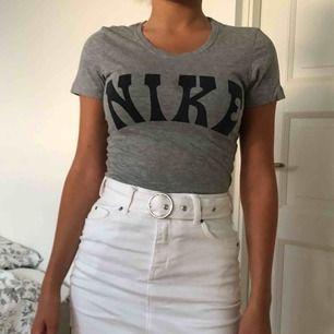Grå snygg T-shirt från märket Nike i storlek XS. Tröjan är i nyskick förutom att det finns en fettfläck längst ner vid sömmen. Denna går att tvätta bort och det är inte svårt att dölja den. Kan mötas upp i Lund eller så står du som köpare för frakt ❤️