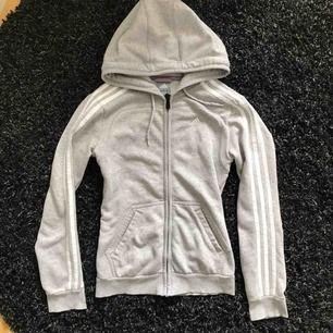 Ljusgrå Adidas hoodie i mycket fint skick. Det står XS i tröjan men jag använde den även när jag var size 36 (S). Längd från axel ca 62cm. Mjuk och skön i lättare bomullsmaterial.