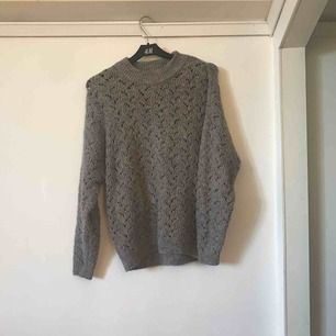 Mitt plagg är en tröja i grått minerat rosa med hål av olika former. Tröjans storlek är xxs- s då den är väldigt stretchig. Tröjan går att använda till näst intill allt och finns även i rosa.