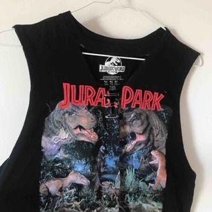 """🦖 Jurassic World tank top från forever 21. Har en utklippt v neck med en """"chocker"""" som lätt går att klippa bort om man skulle vilja. Den är ganska lång men går att klippa. Säljer för 40 kronor + frakt!"""