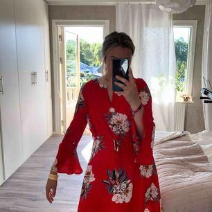 Ett gammalt favorit plagg! Superfin röd klänning med blommor i färgen vit och blå! Köpt för 400kr säljs för 150kr vilket kap! Hör av er vid intresse!