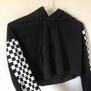 🏁 En croppad långärmad tröja med checkered mönster på båda ärmarna. Den är från hemsidan Shein.