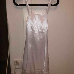 En vit siden klänning med korsning bak Har även spets nertill