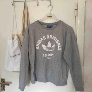 Så cool grå sweatshirt från adidas! Stort vitt tryck fram, använd fåtal gånger och i mycket ba skick. Frakt tillkommer på 59kr🌸