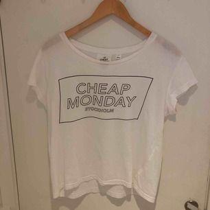 Vit t-shirt från Cheap Monday med svart tryck. Använd några gånger. Köparen står för frakten (30kr) + plaggets pris