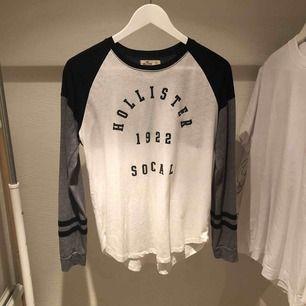 Grå, svart och vit långärmad tröja ifrån Hollister. Tröjan är i storlek XS men passar på mig som vanliga fall har M. Använd 3/4 gånger. Köparen står för frakten (30kr) + plaggets pris