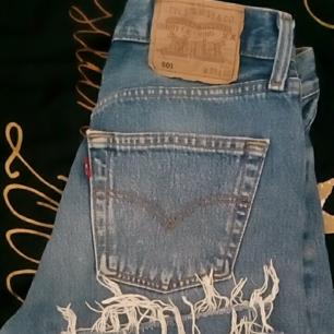 Blåa Levis 501 vintage med slitning nedtill på jeansen.