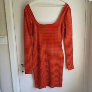 Orange randig klänning från PrettyLittleThing! Aldrig använd. Lika urringad i ryggen som vid bröstet! Går ner till mitten av låren!