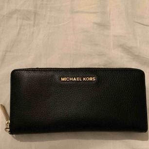 Svart clutch/plånbok från Michael Kors med guldiga detaljer! Använd 1 gång. Kan användas som antingen en mindre clutch eller en större plånbok då den har plats för mobil samt fickor och korthållare etc. Använd endast 1 gång.