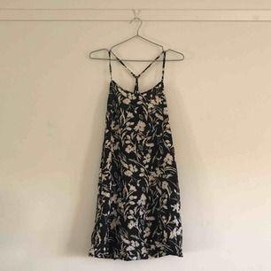 Blommig klänning från weekday med justerbara axelband i vitt och svart.