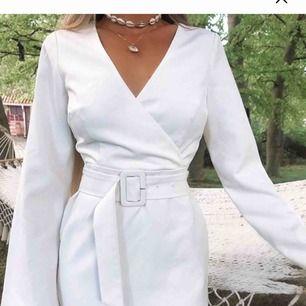En snygg klänning med bälte i midjan och öppen rygg, knappt använd. Slut på storlekar på nakd, först till kvarn