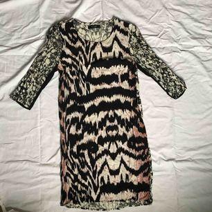 Mönstrad klänning från VILA. Hylsor i sidorna för ett band som tyvärr försvunnit. Använd två gånger och i fint skick. Storlek XS.