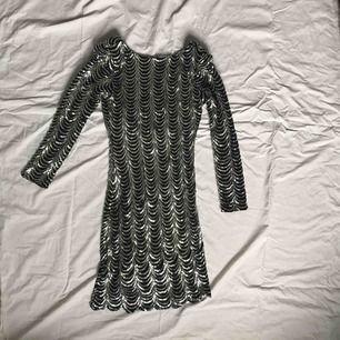 Paljettklänning med mindre axelvaddar från Club L. Urringning i ryggen. Använd en gång, fint skick. Storlek S.