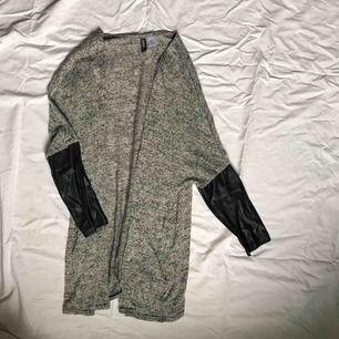 Tunn stickad kofta/tröja från H&M Divided. Skinnimitation på ärmarna. Storlek M.