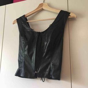 croptop i polyester, liknande läder. dragkedjan har lossnat lite längst ned men sitter med en säkerhetsnål. köpt på emmaus men aldrig använt själv. frakt 9kr.