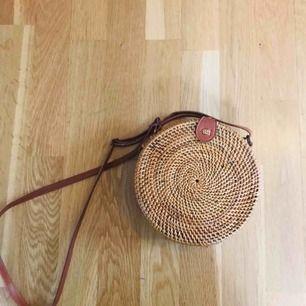 En trendig rund väska med mönstrat tyg inuti. Smalt band som man kan justera om. Väskan stängs med en knapp. Köpt på Bali så har inget märke