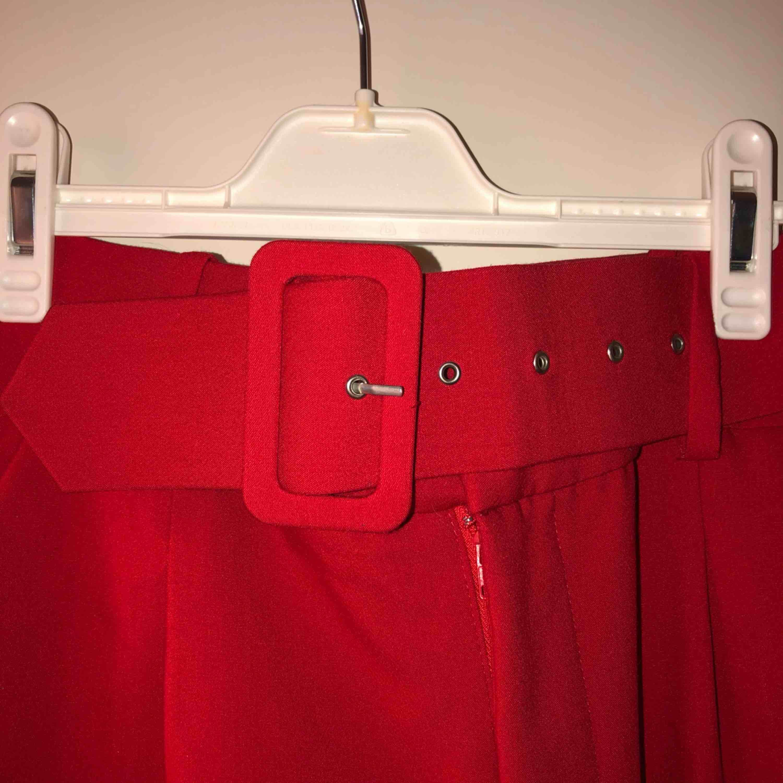 Röda högmidjade kostym byxor med brett skärp, passar s/m  Frakt tillkommer. Jeans & Byxor.