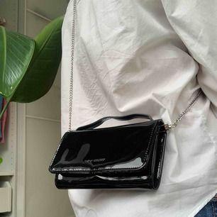 Helt oanvänd väska från Carin Wester. Frakt ingår ej i priset. Svart lack med många fack för ex kort.