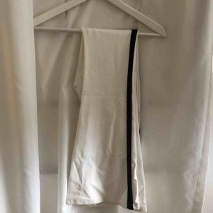 Vita bootcut byxor/tights med svart rand på sidan. Aldrig använd då jag köpte för liten storlek.. jätte snygga på. Fraktar