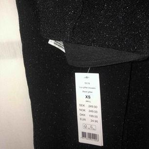 Svarta glittriga byxor med slits (man kan välja om man vill ha slits). Väldigt stretchiga! Det är även som ett pressveck fram på byxan vilket ger att dem samtligt ser lite ut som kostymbyxor. Aldrig använda! Ord.pris 250kr. Fraktar