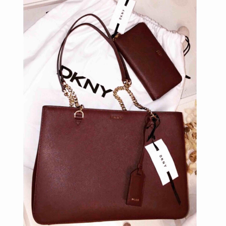ÄKTA DKNY väska + plånbok i färgen oxblood. Använt fåtal gånger, kvitto+dustbag medföljer. Frakt ingår ej! . Väskor.