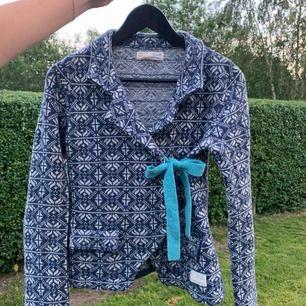 Odd Molly stickad ull omlottkofta med knyte. Sparsamt använd, fint skick. Nypris 1200kr, säljes för 500kr inklusive frakt ( inom Sverige ). Söt mönstrad blå-vit kofta med ljusblå knytrosett.