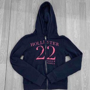 Mörkblå och rosa hollister Hoodie, storlek xs. Frakt kostar 55kr extra, postar med videobevis/bildbevis. Jag garanterar en snabb pålitlig affär!✨ ✖️Fraktar endast✖️