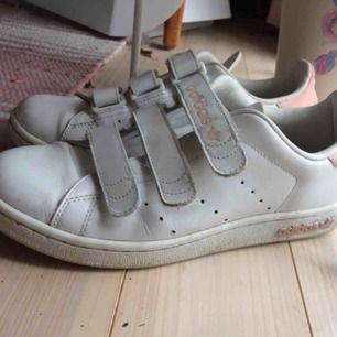 Ett par Adidas skor, väl använda och smått slitna.