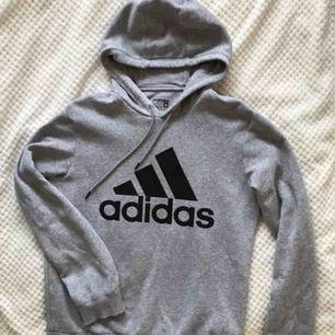 Ljusgrå Adidas hoodie i fint skick. Längd från axel ca 67cm. Stl S Herr, jag har använt den som oversize (stl 34). Frakt 90kr tillkommer.