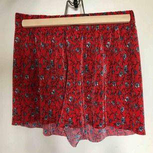 Veckade luftiga shorts i skimrande rött tyg med blommor i gråtoner. Resår i midjan. Frakt max 39kr, kan ev. bli billigare om jag skickar i postorderpåse.