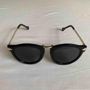 •Svart-guldiga solglasögon med svarta linser •Guldiga detaljer så som pilar på ramarna •Mycket bra skick på linserna •UV-skydd