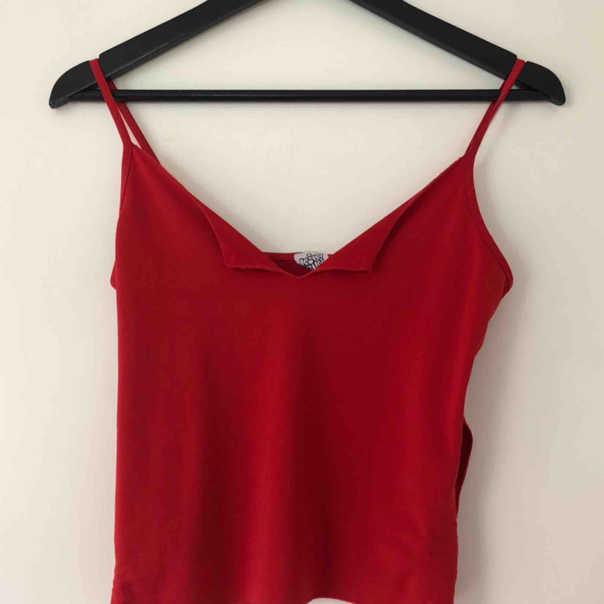 Rött linne med slitsar på sidorna och vid brösten. Stretchigt material. . Toppar.