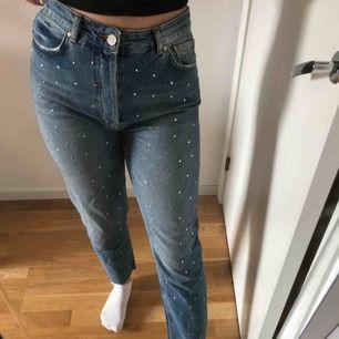 Ett par väldigt coola jeans med strass-stenar på hela framsidan av benen, lite slitningar ned till av benen, stängs med 4 knappar, lite boyfriend jeans modell. ANVÄNDA 1 GÅNG🙌, ordinarie pris 600kr
