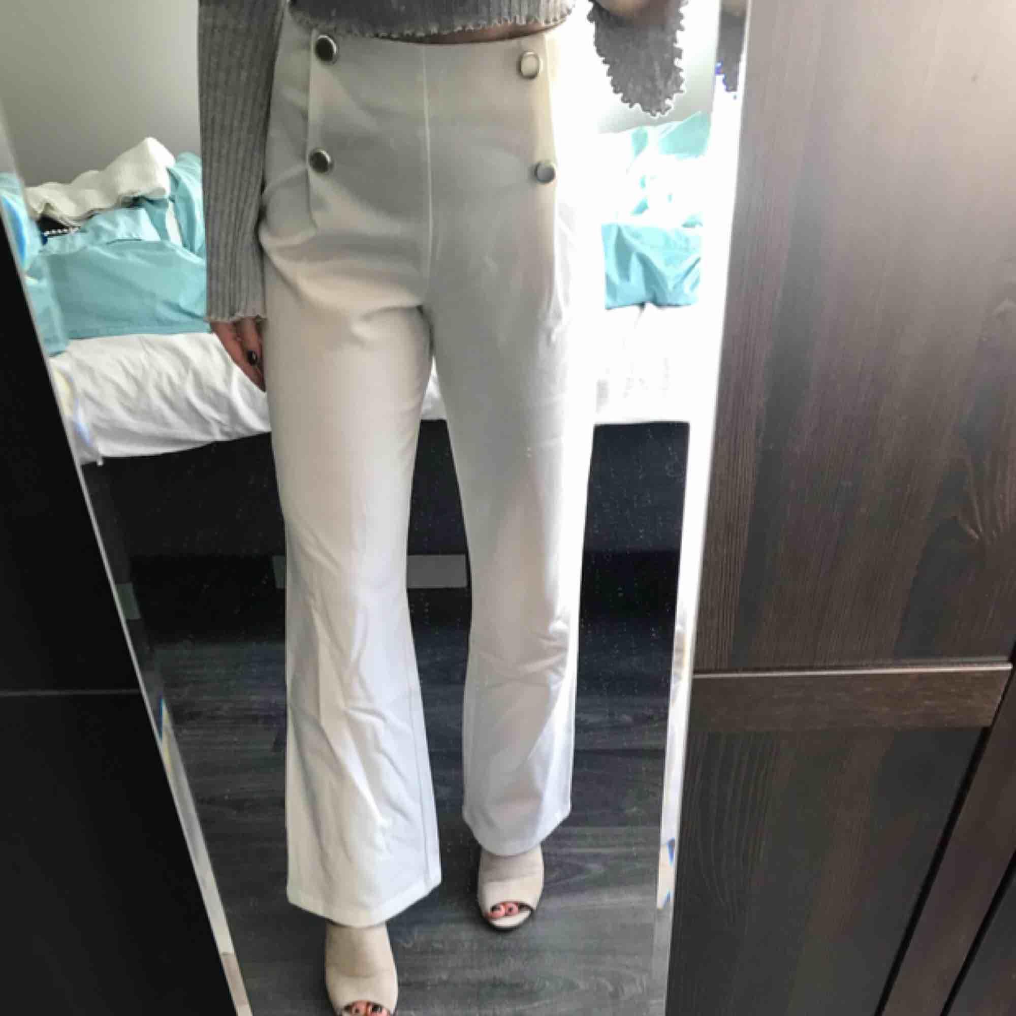 Högmidjade snygga vita byxor med guldknappar. Nypris 399kr endast använda 1 gång! Köparen står för frakt. Jeans & Byxor.