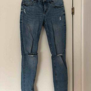 Blåa skinny jeans, mid waist, hål på knäna!