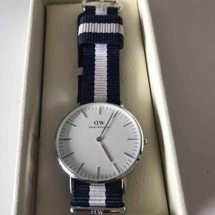 En klocka från Daniel Wellington, aldrig använd. Marinblått och vitt band av tyg. Pris kan diskuteras