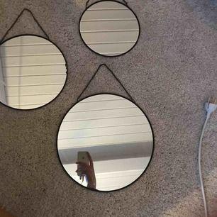 """Tre stycken runda speglar, i olika storlekar. Varje spegel har en svart ram och en svart kedja som""""krok"""""""